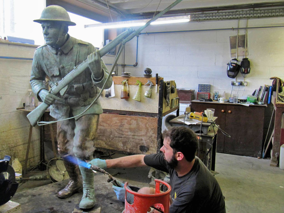 Pat Bull begins the patina on the second soldier for artist Vivien Mallock